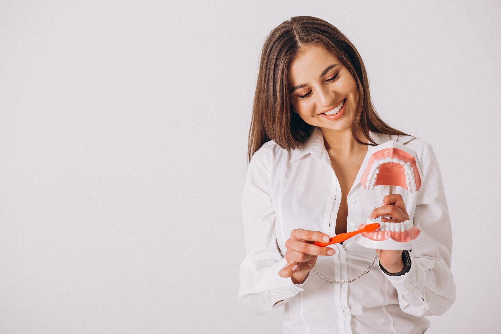 woman brushing a set of prosthetic teeth