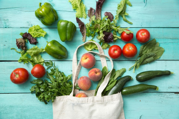 Fresh vegetables burst out of a cloth shopping bag