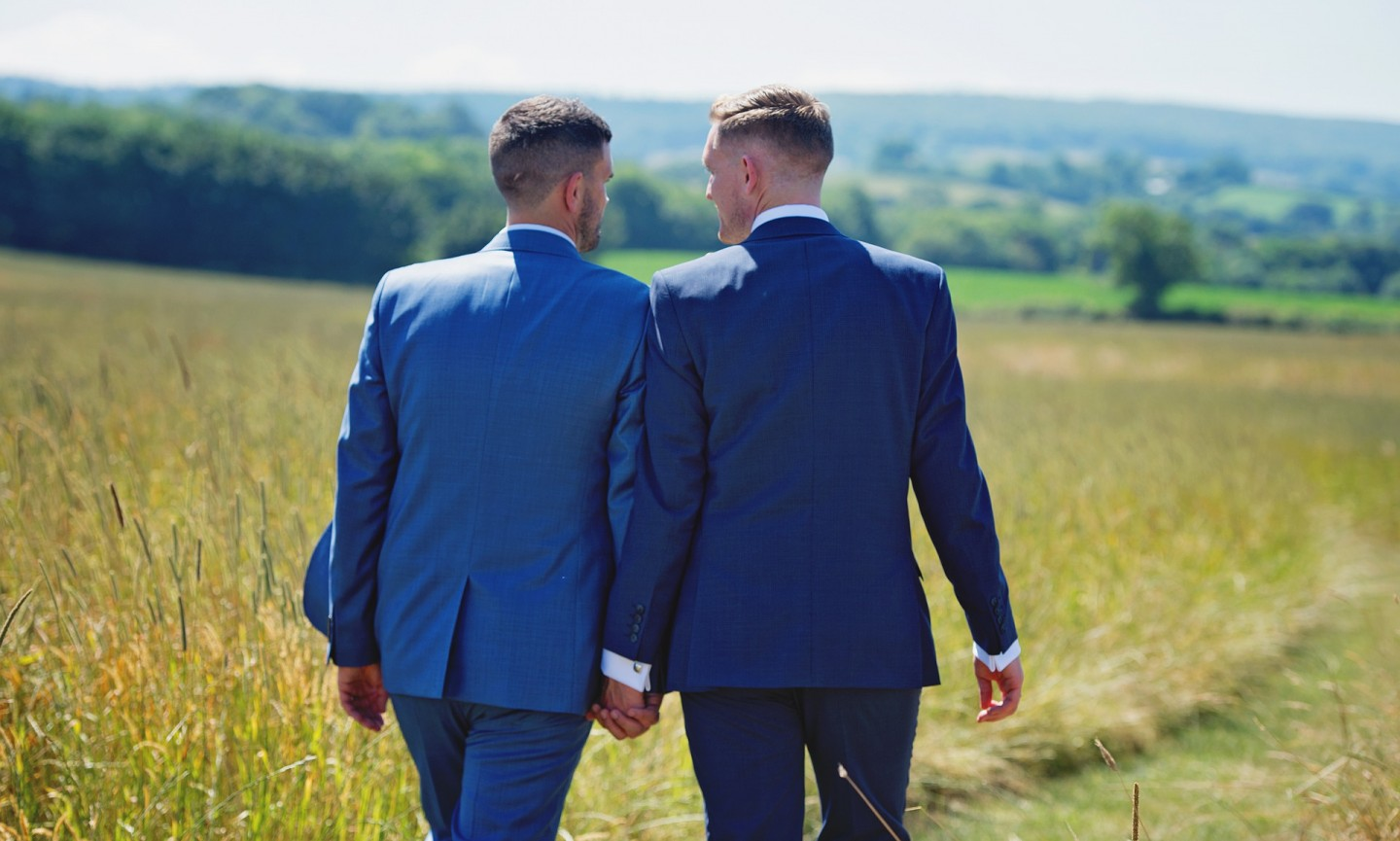 gay male couple holding hands in a field